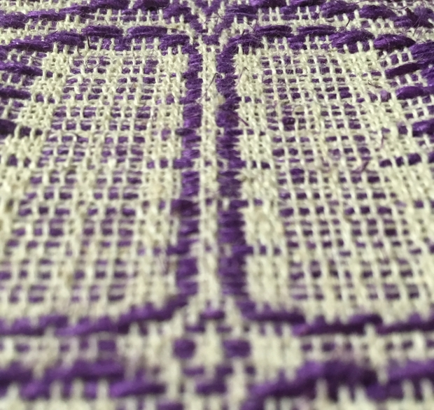 Closeup of handwoven cloth. Thick purple threads weave through thinner undyed threads. The pattern is geometric, the photo is partly out of focus.