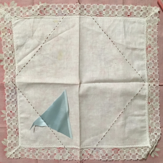 Lace-edged white hanky spread out on top of a larger pink hanky, stitched together with a large diamond shape in dark thread. A fragment of pale blue silk is caught in the stitching.